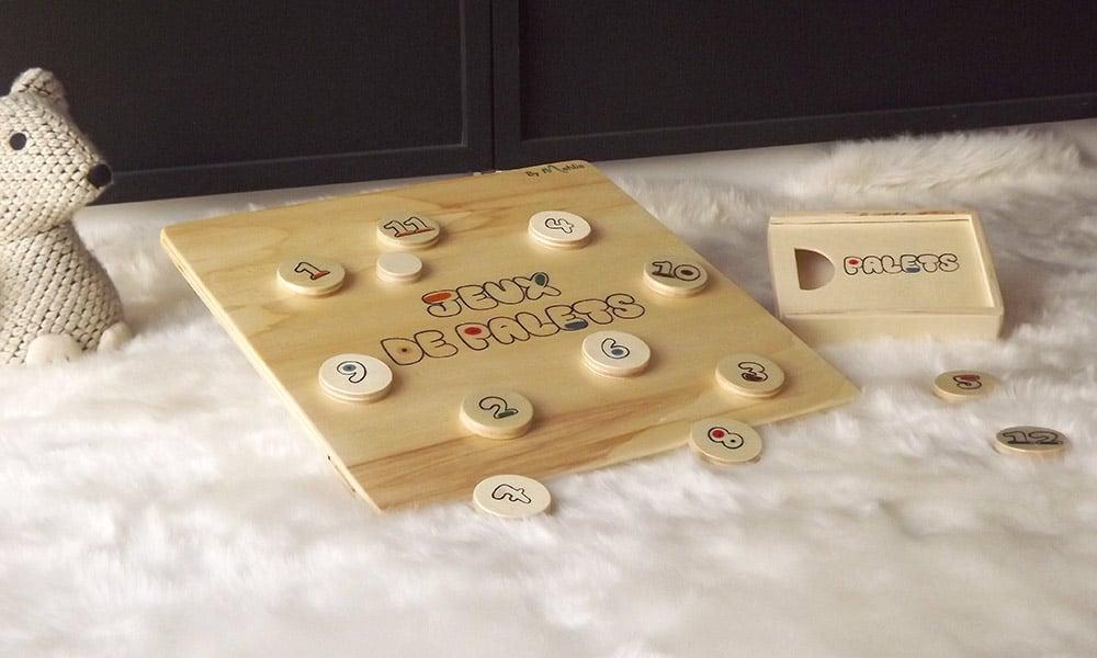 Planche à palets en bois de peuplier et avec une boîte de rangement pour ranger les palets. Ce jouet destiné pour les enfants est fabriqué artisanalement.