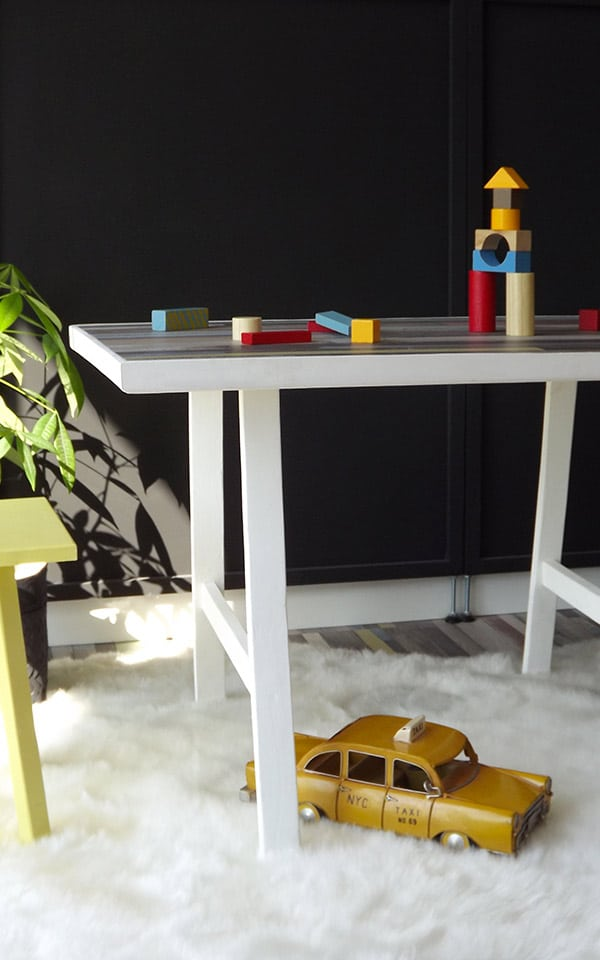 Table enfant avec 2 tabourets jaune et bleu. Cette table dispose d'un plan de travail en parquet stratifié. Certaines décorations sont de Maison du Monde ©