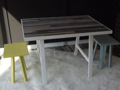Table enfant avec 2 tabourets jaune et bleu. Cette table dispose d'un plan de travail en parquet stratifié.