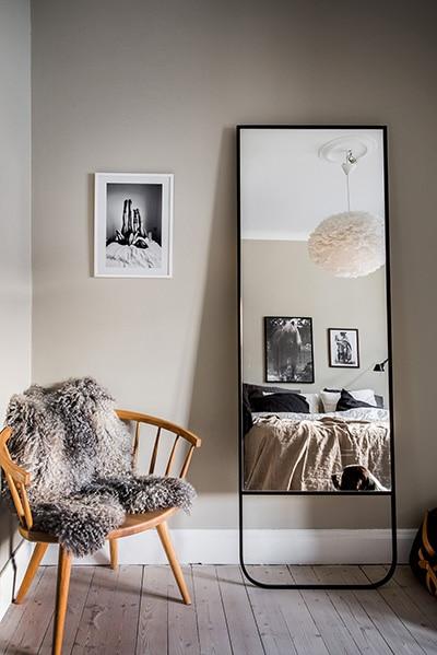 Une décoration scandinave avec son miroir, sa chaise et son plaid imitation fourrure.