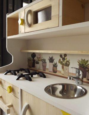 Cuisine en bois jouet pour enfant qui souhaite jouer à la dinette avec les feux, un évier et un robinet