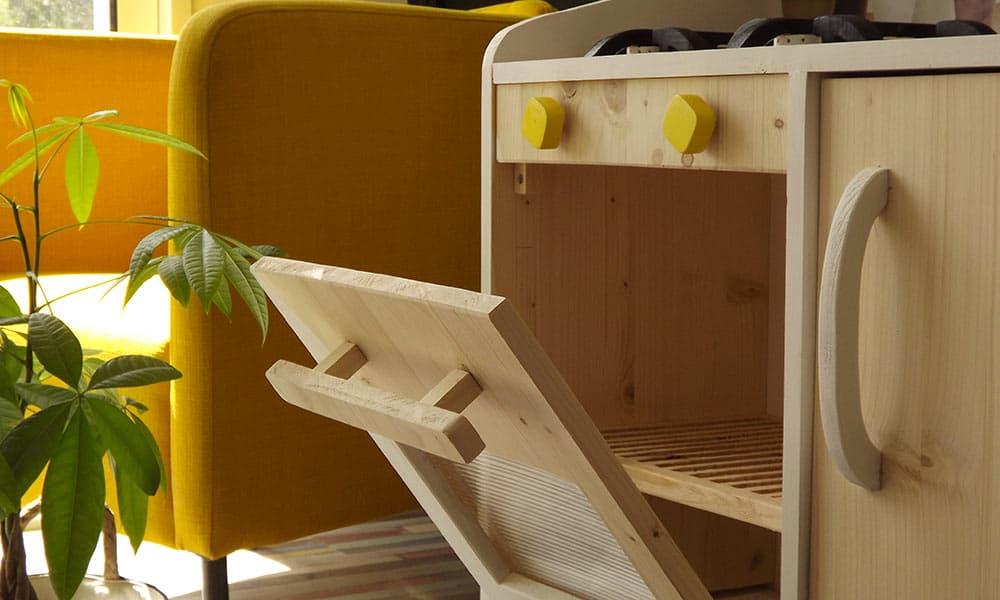 Cuisine en bois jouet enfant avec tous les équipements d'une cuisine moderne comme un four composé de sa grille.