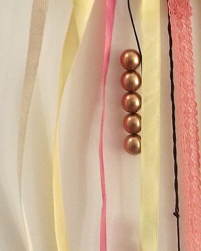 Les perles, les plumes et les rubans de tissu sont les matières premières présentes dans notre attrape-rêves